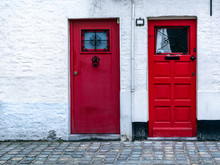 Two Red Wooden Front Doors In The White Brick Wall. Two Vintage Red Doors With Window At The Top.