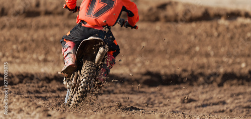 Photo Racer child on motorcycle participates in motocross race, active extreme sport