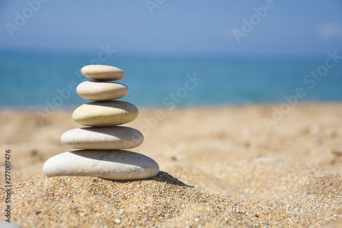 Poster Stenen in het Zand Balanced stone pyramid on sand on beach. Zen rock, concept of balance and harmony
