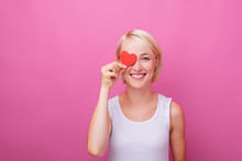 In Love Woman,  Flirting And Putting On Eye, A Little Paper Heart, While Smiling At Camera, Over Pink Isolated Background