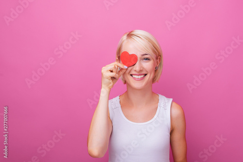 Fotografie, Tablou In love woman,  flirting and putting on eye, a little paper heart, while smiling
