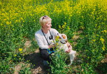 Caucasian Woman Playing With Her Dog In Grass