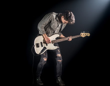 The Musician Plays Bass Guitar, On A Black Background With A Beam Of Light