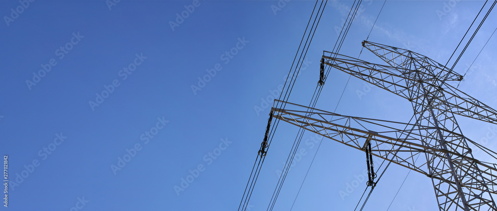 Fototapeta Looking up steel power pylon construction with high voltage cables against blue sky. Wide banner for electric energy industry with space for text on left side