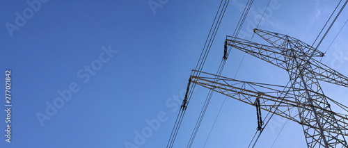 Fototapeta Looking up steel power pylon construction with high voltage cables against blue sky. Wide banner for electric energy industry with space for text on left side obraz