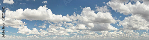 Photo  Wide banner with clouds over flat land, larger at foreground, smaller back in di