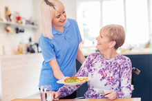 Female Care Assistant Serving ...