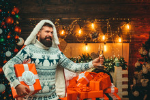 Christmas Man In Santa Hat. Bearded Modern Santa Claus In Knitted Sweater. New Year Christmas Concept. New Year Party.
