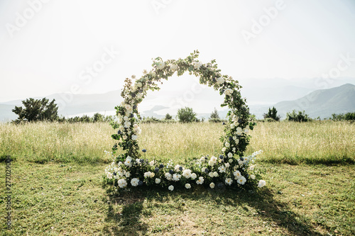 Beautiful wedding arch of flowers or white roses in a field or meadow Canvas Print
