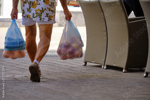 Fotografie, Tablou  Bottom half of unidentified man walking away with fruit and vegetable in multipl