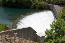 Water Spills Over The Top Of Louros River Hydroelectric Dam And Power Station In A Green Forest In Epirus Greece, Near The Town Of Filippiada
