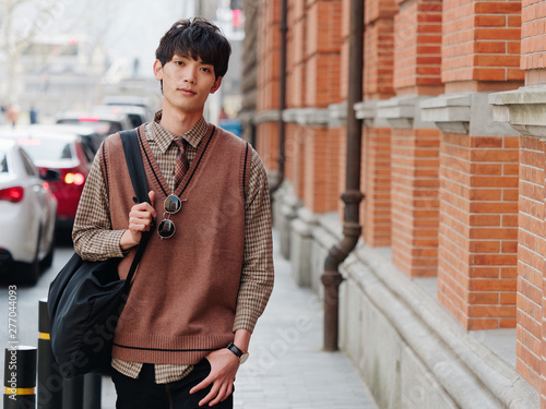 Portrait of a handsome Chinese young man with Korean style clothes walking and looking at camera with sad expression against Shanghai street background, male fashion, cool Asian young man lifestyle Wallpaper Mural
