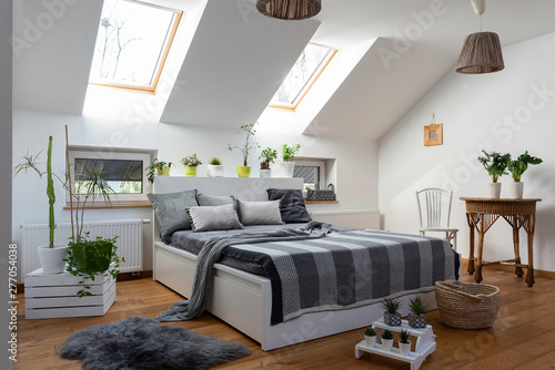 Carta da parati  White bedroom with double bed, grey pillows and green plants in scandinavian style in the attic