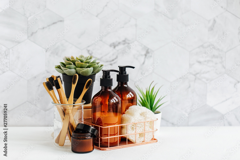 Fototapety, obrazy: Bathroom accessories, natural cosmetics products and tools with green plant on white table inside a bathroom background.