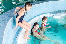 Girls Swim In The Pool. Happy Girls Play In The Pool.Beautiful Girls Swim And Having Fun In Water.Active Holiday.