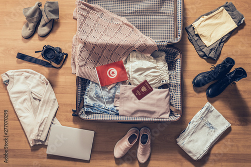 Fényképezés  Woman's clothes, laptop, camera, russian passport and flag of Tunisia lying on the parquet floor near and in the open suitcase