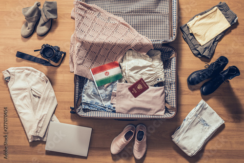 Fényképezés  Woman's clothes, laptop, camera, russian passport and flag of iran lying on the parquet floor near and in the open suitcase