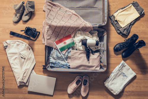 Fényképezés  Woman's clothes, laptop, camera and flag of iran lying on the parquet floor near and in the open suitcase