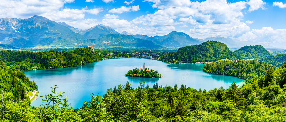 Fototapeta Beautiful landscape of Lake Bled the church island in the middle and the castle in the background of white clouded sky from Ojstrica viewpoint in Bled, Slovenia