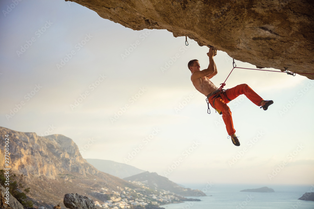 Fototapety, obrazy: Young man climbing challenging route in cave