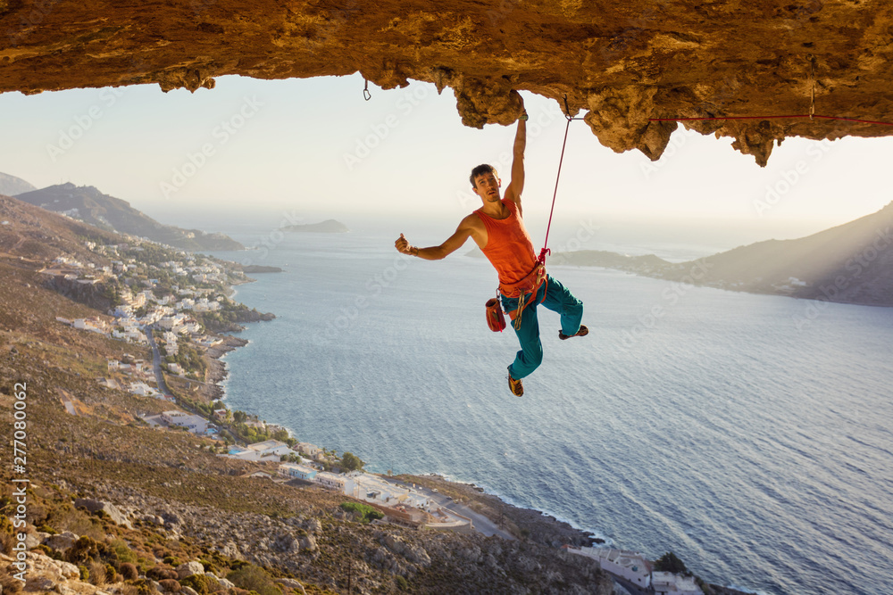 Fototapety, obrazy: Rock climber hanging on cliff with one hand and showing thumb up