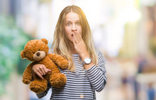 Young Beautiful Blonde Woman Holding Teddy Bear Plush Over Isolated Background Cover Mouth With Hand Shocked With Shame For Mistake, Expression Of Fear, Scared In Silence, Secret Concept
