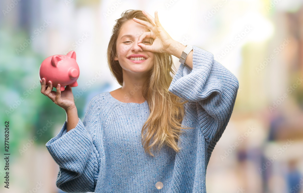 Fototapety, obrazy: Young beautiful blonde woman holding piggy bank over isolated background with happy face smiling doing ok sign with hand on eye looking through fingers