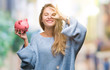Leinwandbild Motiv Young beautiful blonde woman holding piggy bank over isolated background with happy face smiling doing ok sign with hand on eye looking through fingers