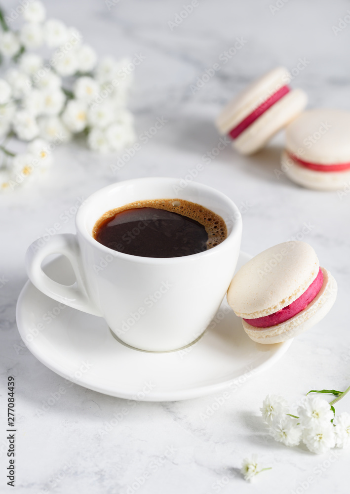 Fototapety, obrazy: A cup of coffee and french macarons on a white marble background. Close-up. Selective focus