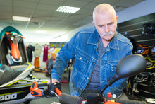 Senior Man Browsing In Motorcycle Shorwoom