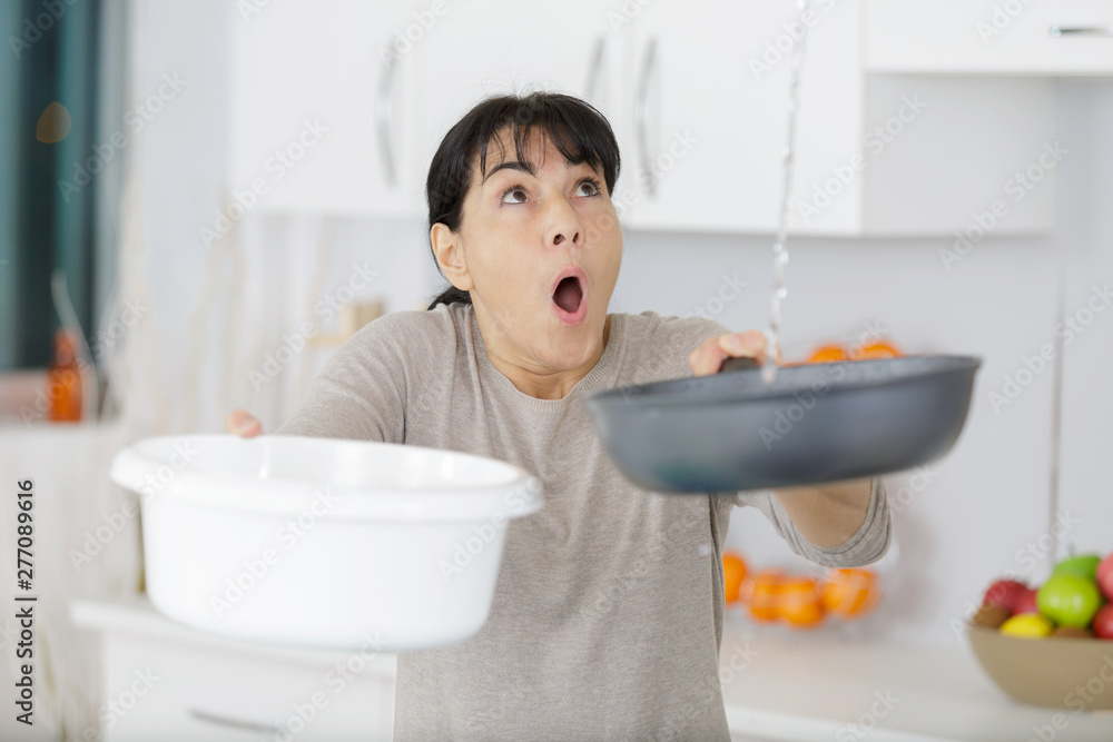 Fototapety, obrazy: woman holding bucket while water droplets leak from ceiling