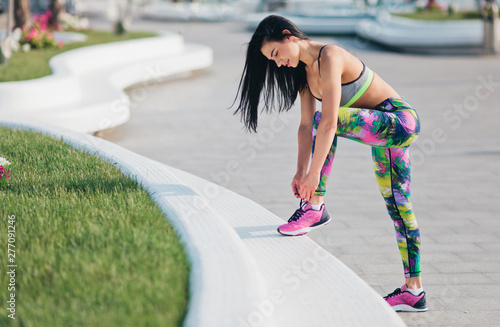 Fotografía  Young sport woman tying shoelace sneakers outdoors