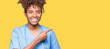 Young African American Doctor Woman Over Isolated Background Cheerful With A Smile Of Face Pointing With Hand And Finger Up To The Side With Happy And Natural Expression On Face