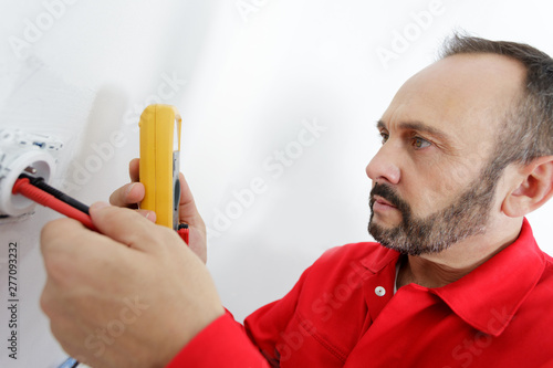 mature male electrician testing socket with multimeter