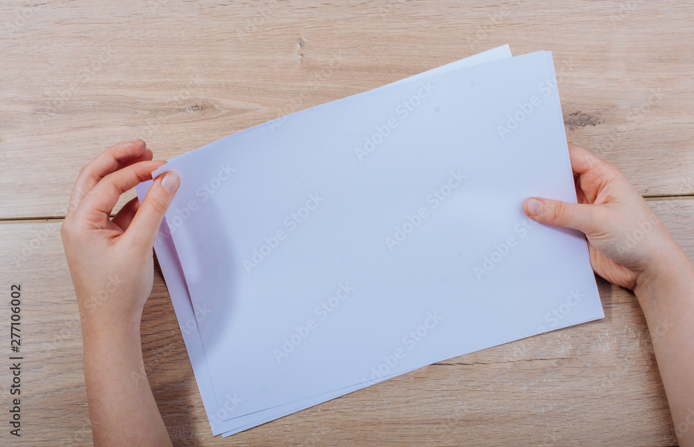 Fototapety, obrazy: Hand holding sheets of paper on wooden background