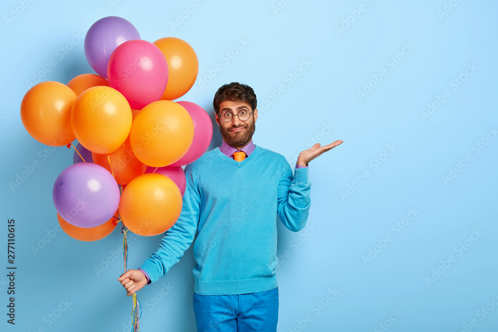 Fototapety, obrazy: Confused hesitant male holiday maker raises palm with puzzlement, tries to make decision, holds multicolored bunch of air balloons, doesnt know whether all guests has come, wears blue clothes