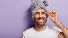 Pampering Concept. Handsome Cheerful Man Plucks Eyebrows With Tweezers, Cares About Beauty, Has Towel On Head, Morning Hygiene, Smiles At Camera, Wants To Look Nice, Shapes Brows, Stands Indoor