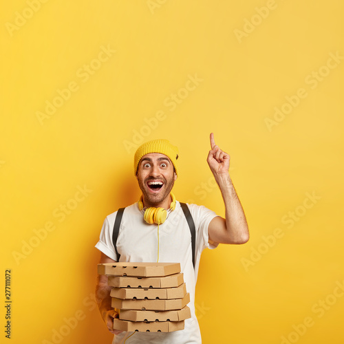 Photo  Glad delivery man has joyful expression, points up, shows where pizzeria situated, carries pile of pizza boxes, distributes product for customer, isolated on yellow wall
