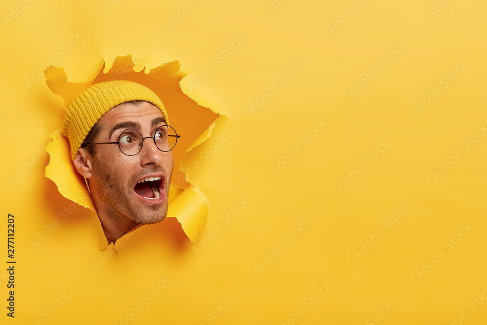 Fototapety, obrazy: Overwhelmed young guy keeps head through torn hole in yellow background, keeps jaw dropped, gazes aside on free space, notices something surprising, wears hat and big round glasses. Reaction