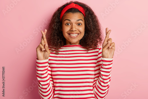 Attractive curly haired woman crosses fingers, anticipates good news, grins hopefully, wears red headband and striped jumper, hopes for good luck, isolated on pink background Tableau sur Toile