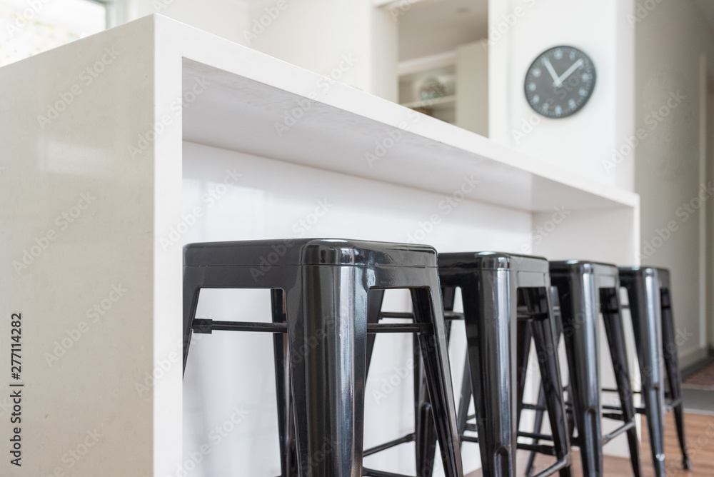 Fototapety, obrazy: Closeup of black metal stools against white kitchen bench with clock in background (selective focus)