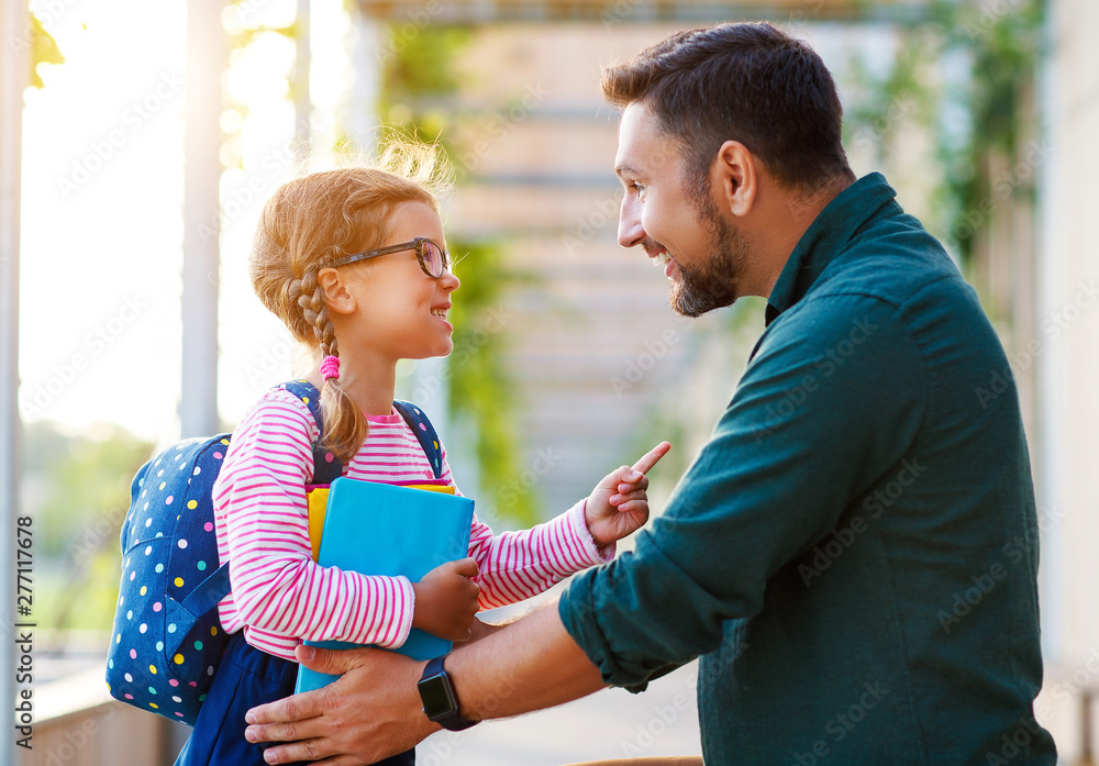 Fototapety, obrazy: first day at school. father leads  little child school girl in first grade.