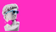 canvas print picture - Statue. Earphone on a pink background. Gypsum statue of David's head. Creative. Plaster statue of David's head in blue sunglasses. Minimal concept art.
