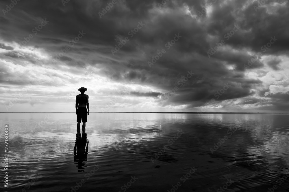 Fototapeta Moody monochrome silhouette of man in hat standing in calm shallow waters reflecting dramatic skyscape on the sea horizon