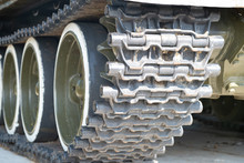 A Tank Of The Second World War. Caterpillar Armored Closeup Shot. Black Track Link And Large Rubber-coated Rollers. Chassis Tank. Tank Tracks.