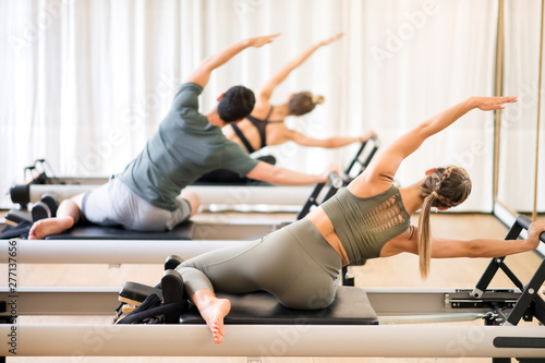 Fotografie, Tablou  Group of people doing the mermaid pilates exercise