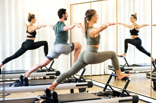 Fotografia  Class in a gym doing pilates standing lunges