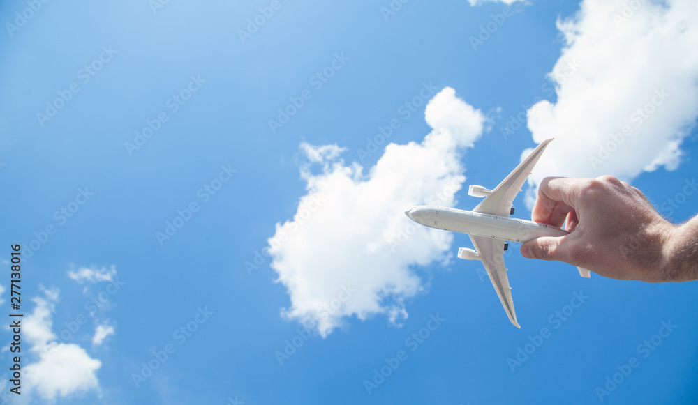 Fototapety, obrazy: Hand holding airplane model in front of blue sky background. Travel