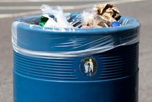 Overflowing Blue Metal Public Waste Bin With Plastic Liner