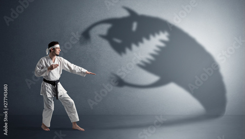 Cuadros en Lienzo Young karate man fighting with a big black scary shadow